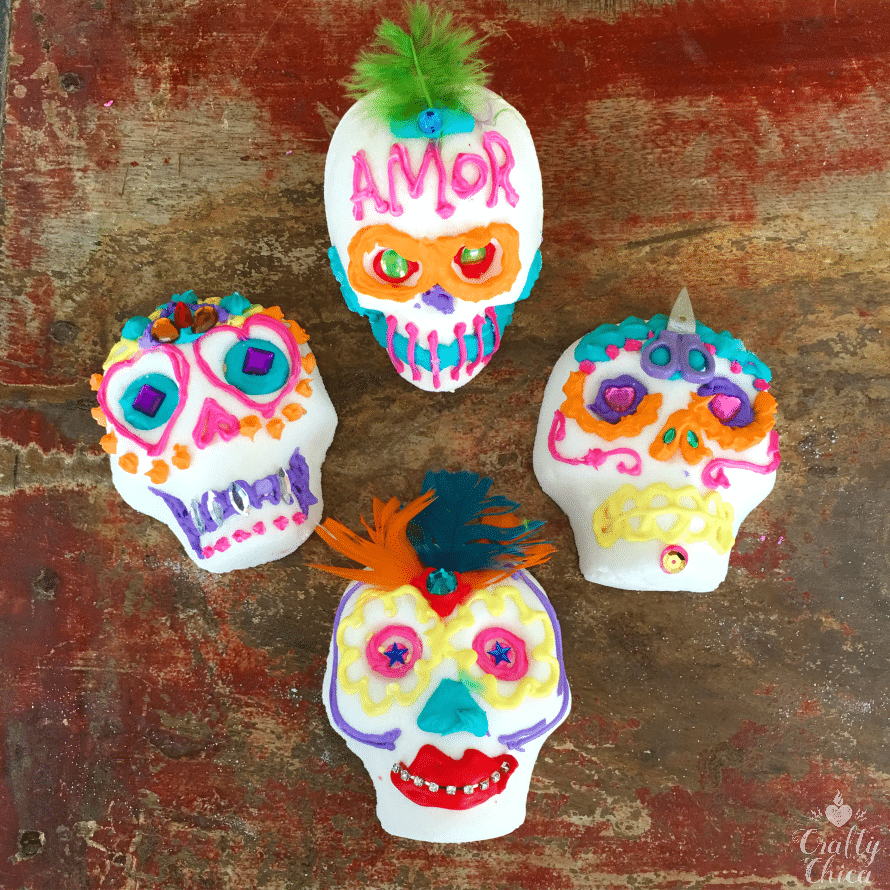 Colorful decorated sugar skulls with feathers, icing and gems.